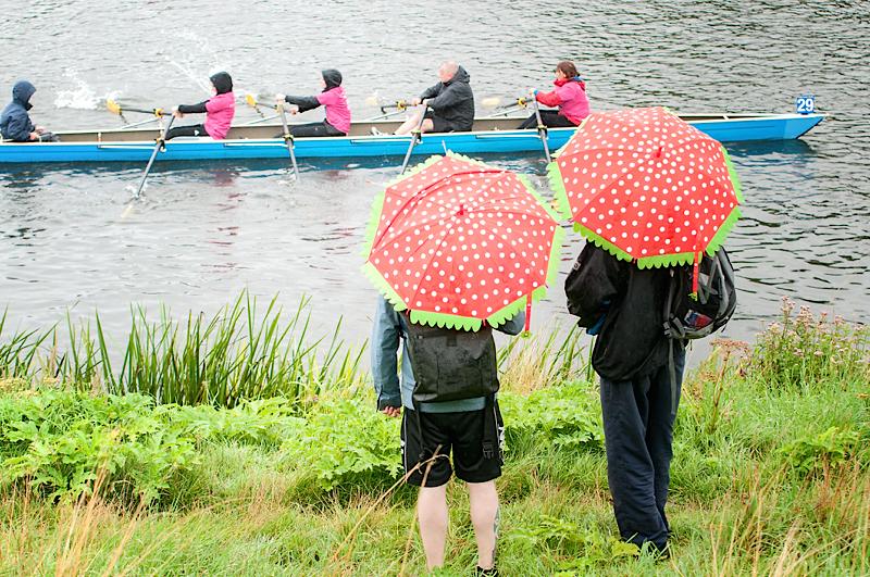 zwei Männer am Ufer mit roten Schirmen