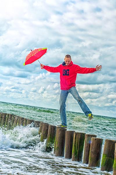 Mann am Meer mit Schirm