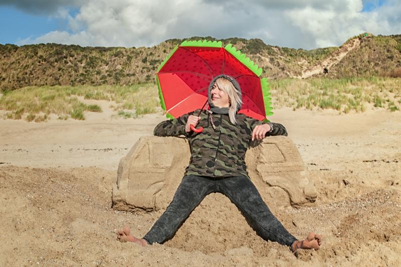Frau am strand sitzend mit rotem Schirm