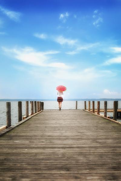 Frau am ende von einem Steg mit dem roten Schirm