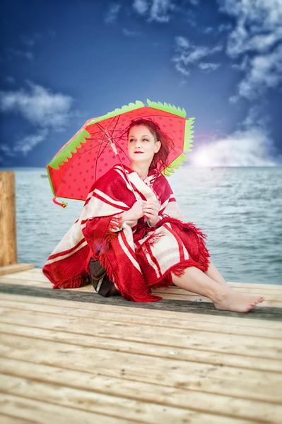 Frau mit rotem Schirm am Wasser