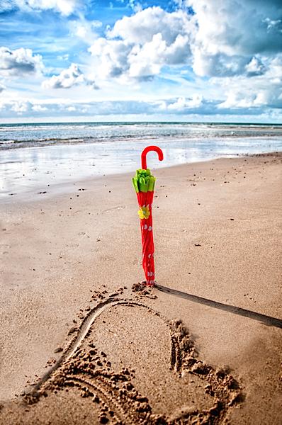 Roter Schirm allein am Strand