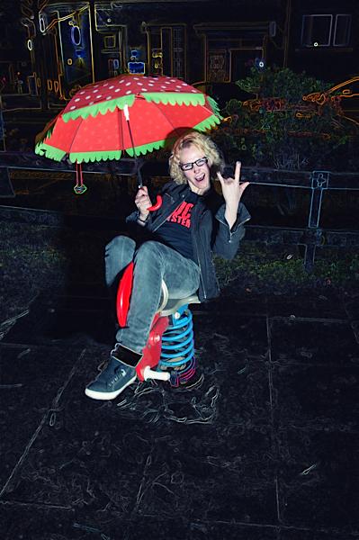 Frau auf Spielplatz mit Schirm