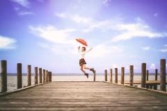 Frau springend am ende vom Steg